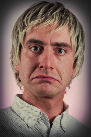 Sad blonde haired man frowns in studio portrait