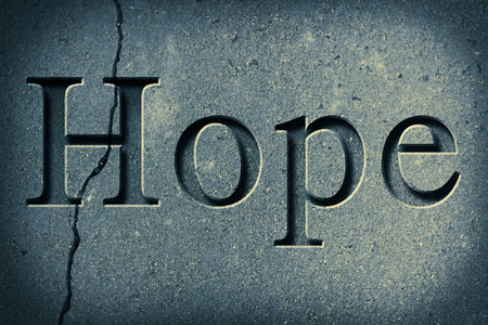 chiseled: Engraving spelling the word Hope on textured old surface