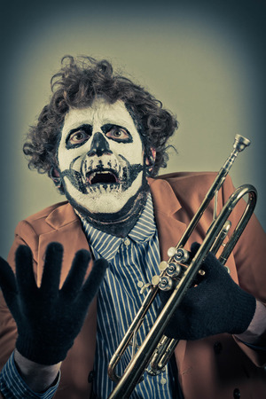 trumpet player: Pleading trumpet player with face painted as human skull