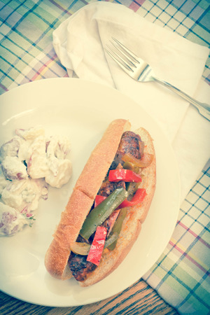 Fried sausage onions and red and green bell peppers on sandwich bun Standard-Bild