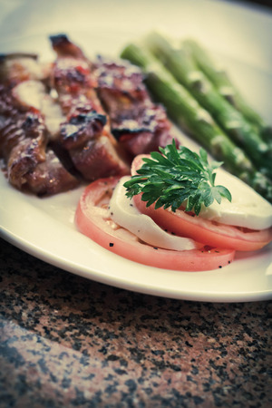 Honey glazed chicken with asparagus and caprese salad Banque d'images