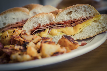 kaiser: Taylor ham, pork roll, egg and cheese breakfast sandwich on a kaiser roll with salt pepper and ketchup and a side of home fries from New Jersey