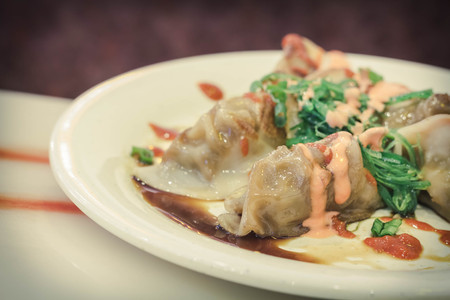 hot sauce: Fancy szechuan dumplings topped with sriracha hot sauce spicy mayonnaise and seaweed salad