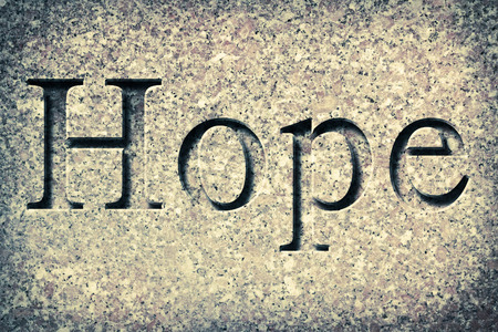 Engraving spelling the word Hope on textured old surface