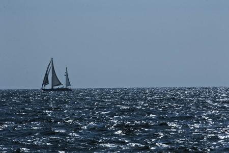 ketch: Stylized vintage sailboat riding along a cloudy horizon Stock Photo