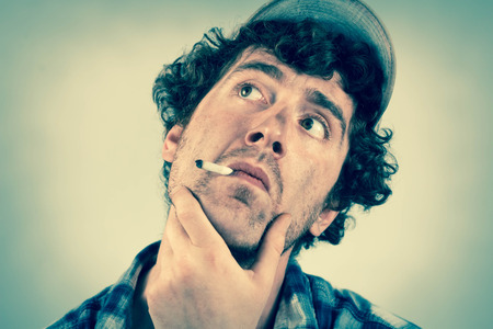 ignorant: Thinking redneck dwells on many thoughts as he smokes a cigarette Stock Photo