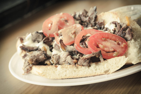 horseradish sauce: Messy cheesesteak sandwich with sliced tomatoes and a rich creamy horseradish sauce with side of macaroni salad Stock Photo