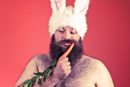 Childish bearded fat man wears silly bunny ears