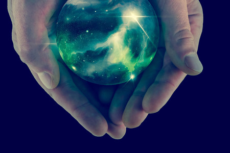 Holding the universe in fortune teller magic crystal ball Stockfoto