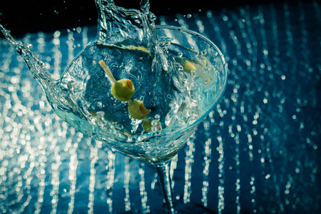 toothpick: Splashing dirty martini garnished with green olives on toothpick Stock Photo