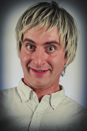 cynical: Grinning silly man with blonde hair and wide eyes Stock Photo