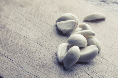 garlic cloves: Fresh pealed garlic cloves on used and worn wooden cutting board for food ingredient background