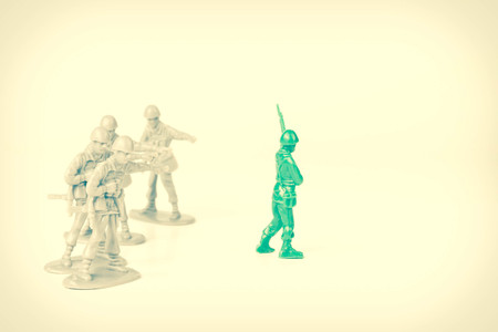 loner: Gray toy soldiers pointing and bullying a green toy soldier