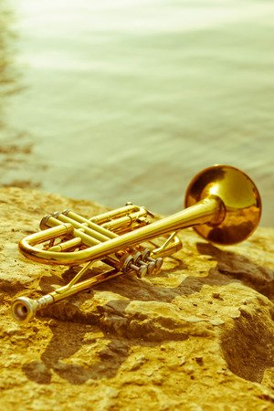 Summer Jazz trumpet in nature lying on rocks lakeside Stok Fotoğraf
