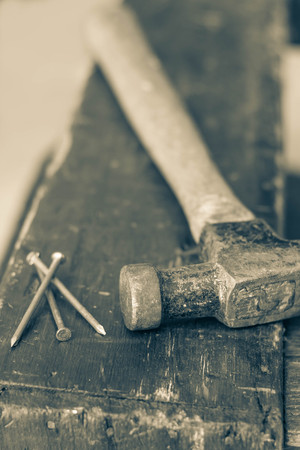 contracting: Old and worn contracting hammer and three nails on a distressed work bench