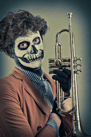 trumpet player: Confident trumpet player with face painted as human skull