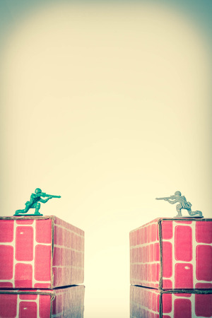 sibling rivalry: Rival toy army men aim guns at eachother atop opposing toy bricks