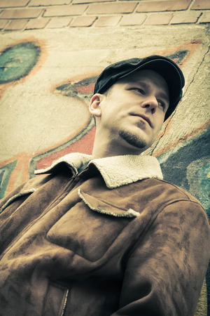 early thirties: Cool guy rocks an aviator jacket and newsboy cap as he takes a moment to think