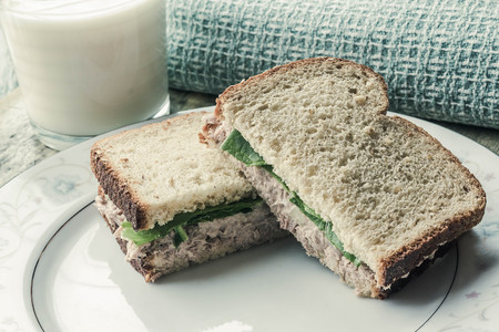 food and beverages: Whole wheat tuna salad sandwich with a glass of milk