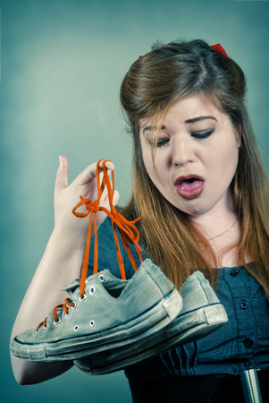 gagging: Cute girl holds up two smelly stinky sneaker shoes