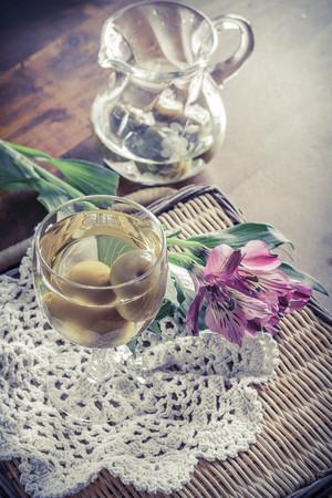 fiori di campo: Dolce vino di prugne giapponesi con frutta in vetro fotografato con bellissimi fiori rosa