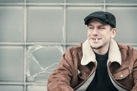 newsboy cap: Cool guy in aviator jacket and newsie cap relaxes against a glass wall as he smiles a silly grin