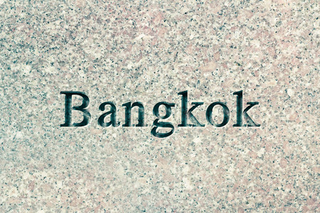 chiseled: Engraving spelling the city Bangkok on textured old surface