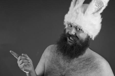 Tattling bearded fat man wears silly bunny ears