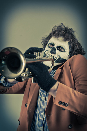 virtuoso: Professional trumpet player with face painted as human skull Stock Photo