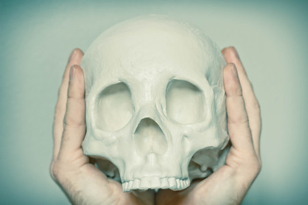death head holding: Hands hold skull in the air for pensive expression