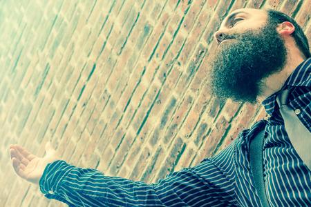 hombre barba: hombre de la barba bien vestido levanta la mano a un poder superior