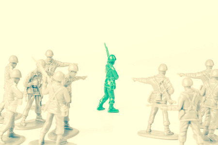 Gray toy soldiers pointing and bullying a green toy soldier