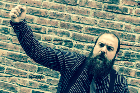 dismay: Well dressed bearded man raises his fist in dismay