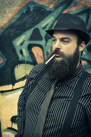 hombre barba: Hombre barbudo Snazzy fuma un cigarrillo en una calle de la ciudad