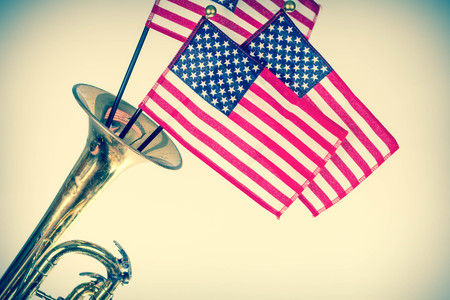 erupt: Three American Flags erupt from the bell of a trumpet in patriotism image Stock Photo