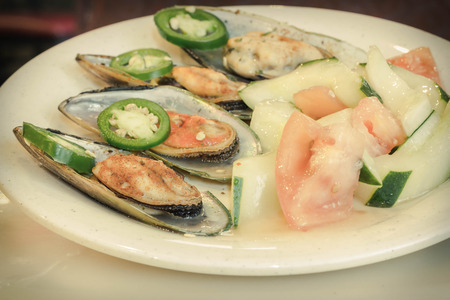 Spicy chili mussels with jalapeno slices and cucumber tomato salad