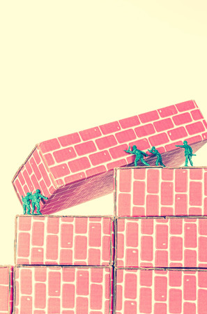 green plastic soldiers: Green army men using teamwork to make progress up the toy brick stairs