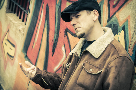 loitering: Cool guy rocks an aviator jacket and newsboy cap as he weighs his options Stock Photo