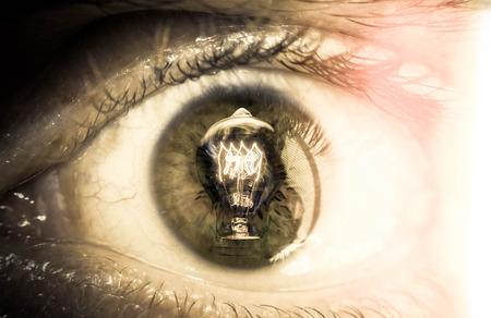 cornea: Conceptual lightbulb reflection in closeup macro of male eyeball