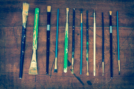 fine tip: Old used paintbrushes on worn rugged painters desk surface arranged in repetitive pattern Stock Photo