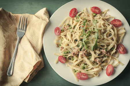 alfredo: Italian health conscious fettuccine alfredo with halved cherry tomatoes and arugula garnish Stock Photo
