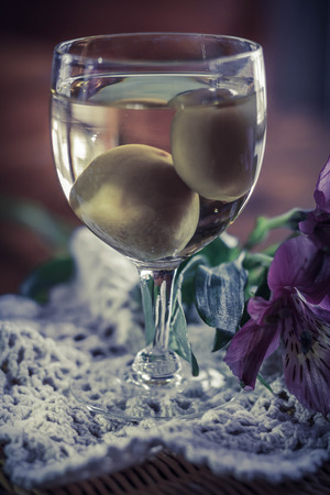 fleurs des champs: Douce japonaise vin de prune avec des fruits dans le verre avec de belles fleurs sauvages photographié roses Banque d'images