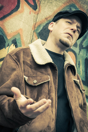 early 30s: Cool guy rocks an aviator jacket and newsboy cap as he weighs his options Stock Photo