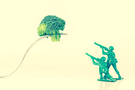 green military miniature: Green army men attack a threatening kitchen fork