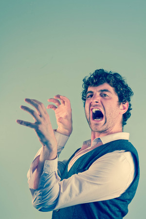 clawing: Man acting like an animal by growling snarling and clawing Stock Photo