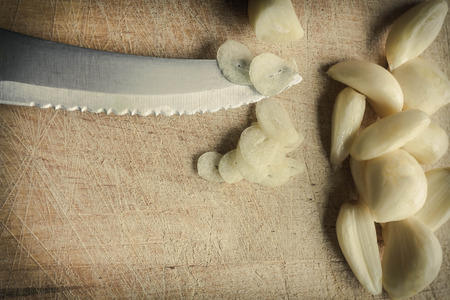 garlic cloves: Fresh pealed garlic cloves chopped on used and worn wooden cutting board for food ingredient background