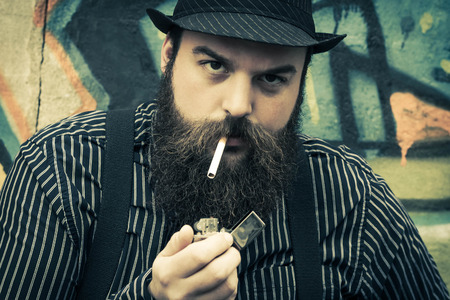 snazzy: Snazzy bearded man smokes a cigarette on a city street
