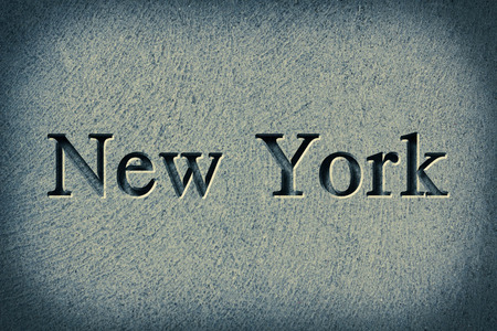 Engraving spelling the city New York on textured old surface