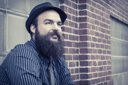 hombre con barba: Hombre barbudo Elegante sienta contra un edificio completamente satisfecho ladrillo