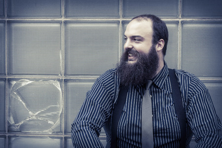 well dressed: Well dressed happy bearded man sits against a glass building